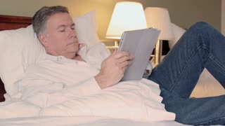 man in a hotel room using a tablet pc smiles at camera