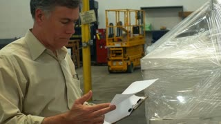 man in a large warehouse looking at a clipboard 4k