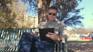 man in a park looking at a tablet pc.