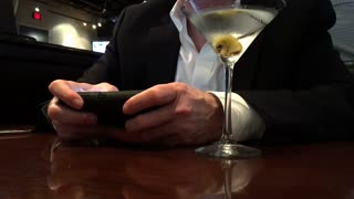 man in a restaurant texting on his smart phone and drinking a martini