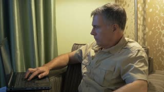 man in his hotel room using a laptop