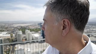 man looking at the city below him on the rooftop of a hotel 4k