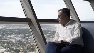 man looking out the window from a highrise hotel 4k