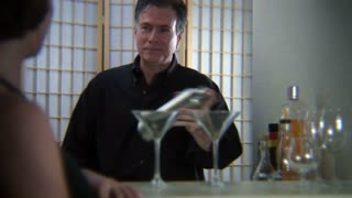man mixing drinks for a woman