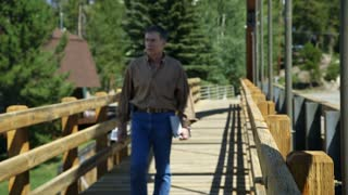 man on a bridge walks past camera.