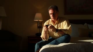 man on bed texting and thinking