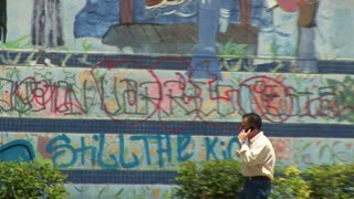 man on the phone next to a graffiti wall