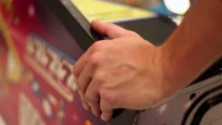 man playing a pinball machine
