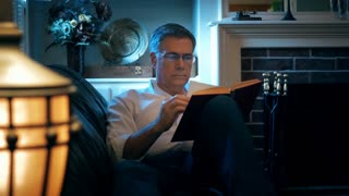 man reclining on his couch reading a book 4k