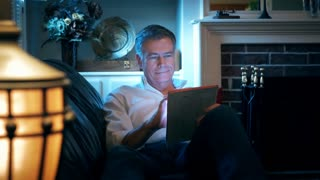 man reclining on his couch using an electronic tablet 4k