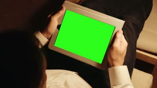 man relaxes with a tablet pc green screen.