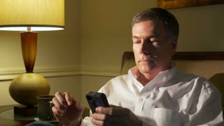 man relaxing on a couch using his smart phone 4k.