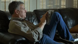 man relaxing on his couch drinking coffee using a tablet pc