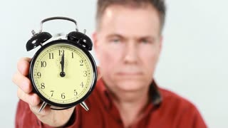 man showing ringing alarm clock
