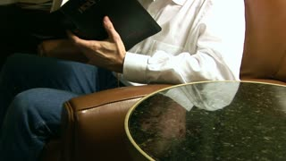 man sitting in a chair in prayer and  with bible