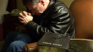 Man sitting in a chair praying