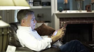 man sitting in his living room looking at a tablet pc 4k