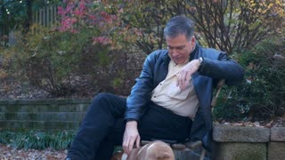 man sitting on a park bench playing with his dog
