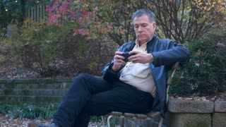 man sitting on a park bench texting with his smart phone