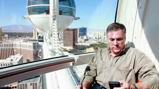 man talking on the phone of a giant ferris wheel in Las Vegas.