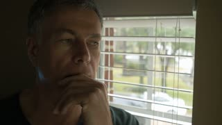 man thinking of something serious and looks out window