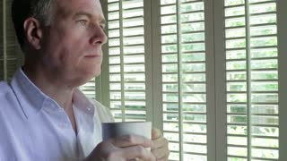 Man thinking with coffee while looking out a window.