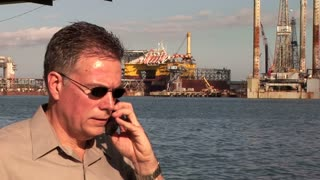 man using a cell phone on oil rigs