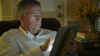 man using a tablet pc in a dimly lit room.