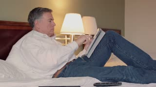 man using a tablet pc in his hotel room