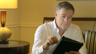 man using a tablet pc smiles at camera.