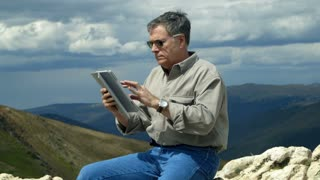 man using a tablet pc while on a mountain.