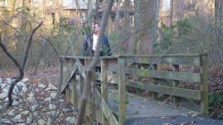man walking across a wooden bridge past camera
