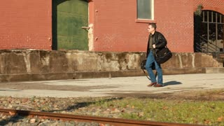 man walking across the tracks