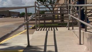 man walking on crutches on a handicap ramp