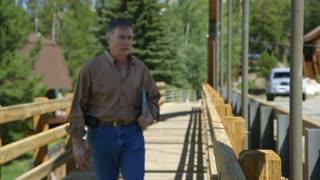 man walks and stops on bridge walkway