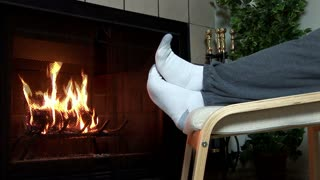man warming feet next to a fireplace