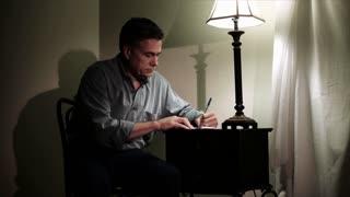 man writing at a small desk