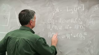 man writing scientific equations on a chalk board.