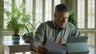mature man at home with tablet pc working on financials