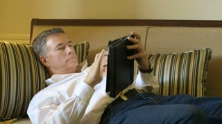 mature man lying on couch using a tablet pc