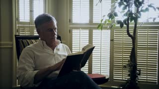mature man reading a book then stops to think 4k