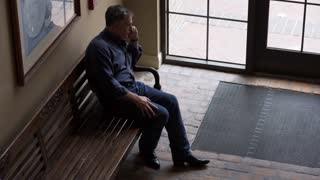 mature man sitting on a bench in an old hotel using his cell phone 4k