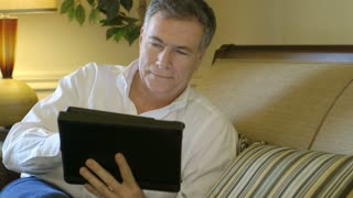 mature man smiles while using a tablet pc.
