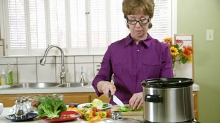 mature woman in the kitchen smiles at camera