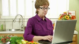 mature woman in the kitchen using a laptop smiles at camera.