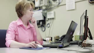mature woman network administrator working in office takes helpdesk call