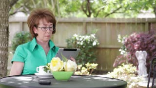 Mature woman outdoor with a tablet pc.
