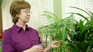 mature woman tending to her plants smiles at camera.