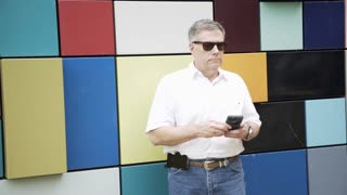 middle age man taking photos with his smartphone next to a multi colored wall 4k
