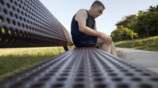 middle age man with knee pain on a park bench 4k